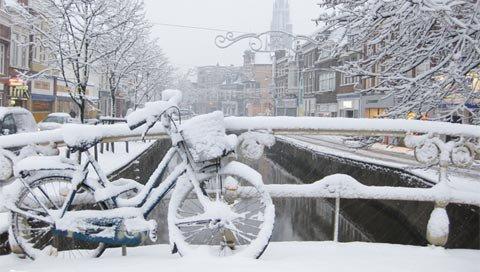 stedentrip nederland besneeuwde gracht en fiets